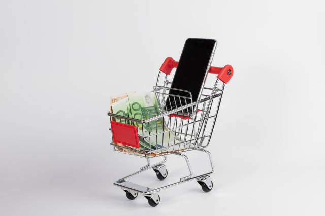 Smartphone with Euro banknotes in shopping cart