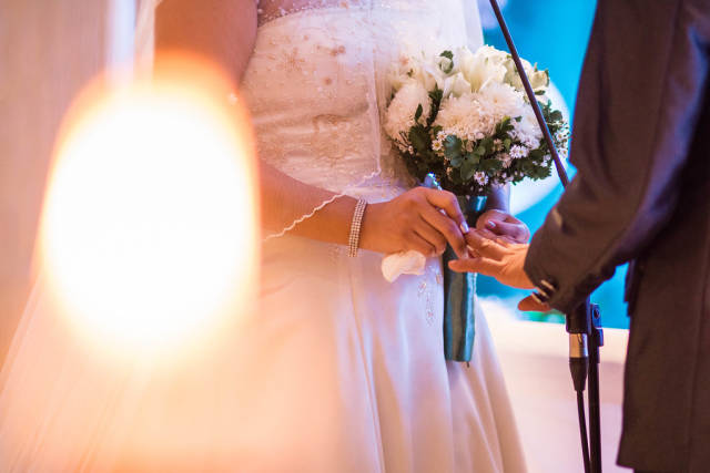 Bride inserting wedding ring to Grooms finger