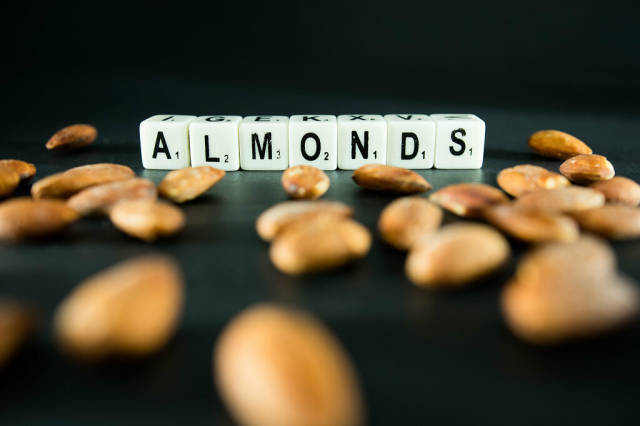 Dice reading ALMONDS with almonds around
