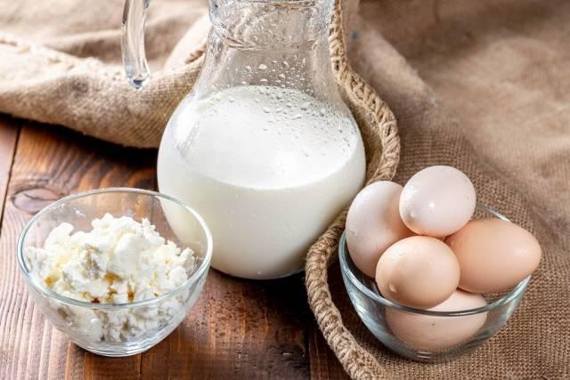 Gläserne Kanne mit frischer kalter Milch neben Glasschale mit Hüttenkäse, Eiern und Jutesack