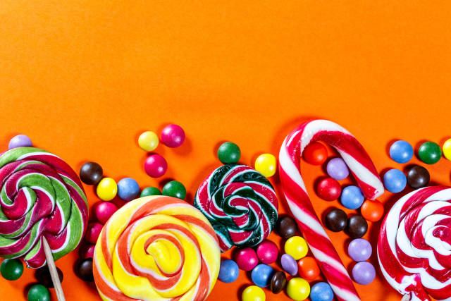 Colorful lollipops and candies on orange background