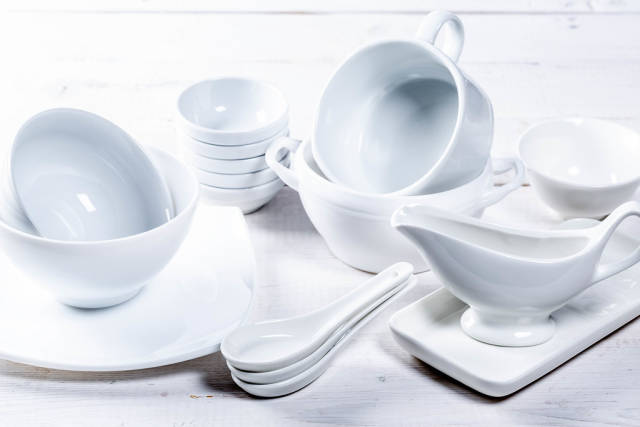 Set of different white dishes on white background