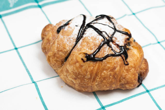 Delicious fresh pastry croisant with chocolate and powdered sugar