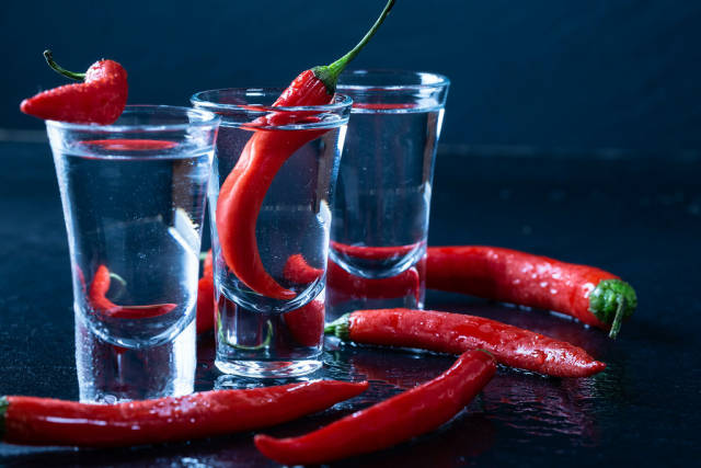 Spicy red chili with vodka glasses on black background