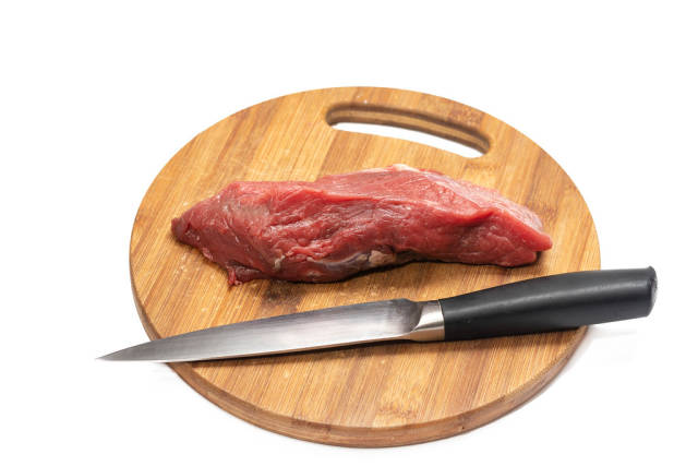 Kitchen knife and beef meat on the round wooden board