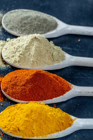 Fresh ground spices in wooden spoons