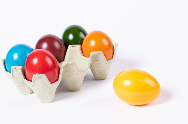 Colored Easter eggs in a box on white background