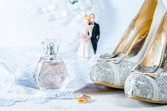 Hochzeits-Szenario mit Trauringen, Parfumflakon, Brautschuhen und Brautpaar-Figur auf weißer Spitze