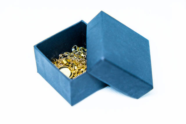 Gold jewelry in a box on white background