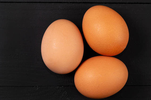 Closeup on Three Chicken Eggs on the black background