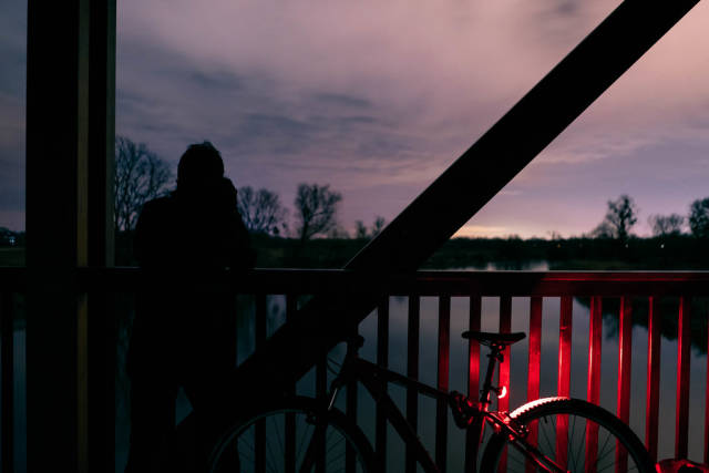 A man taking a picture on the wooden bridge by a bicycle at night