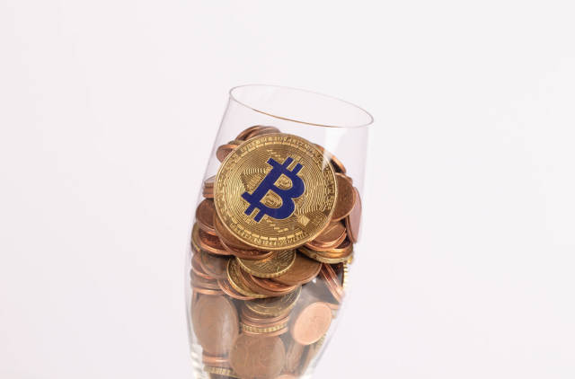 Golden Bitcoin and coins in champagne glass
