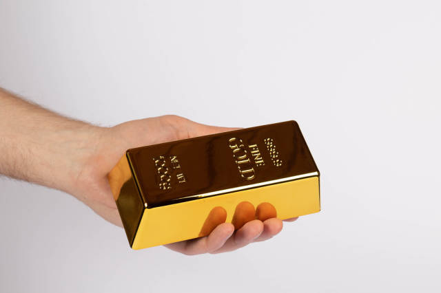Hand holding a gold bar on white background
