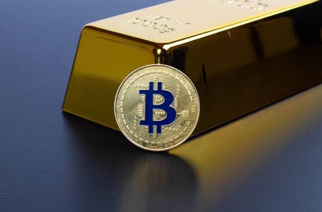 Goldbarren mit goldenem Bitcoin vor schwarzem Hintergrund