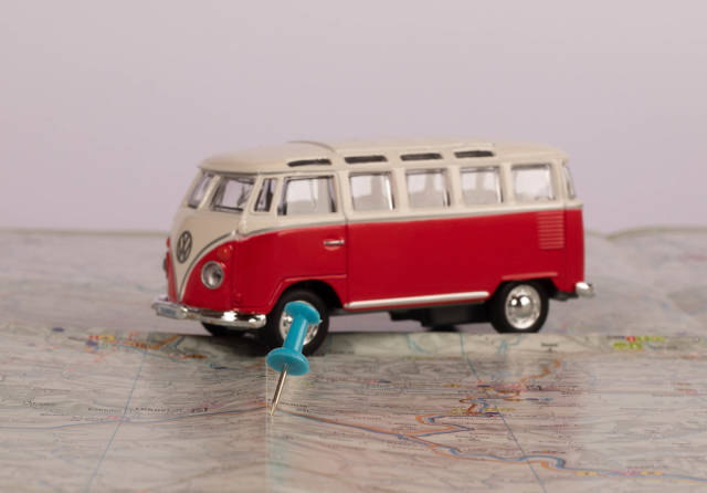 Pushpin with vintage camper van on map