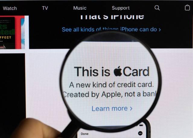 """Text mit eingebautem Logo von """"This is Apple Card"""", wirbt für eine Kreditkarte,  vergrößert durch eine Lupe dargestellt"""
