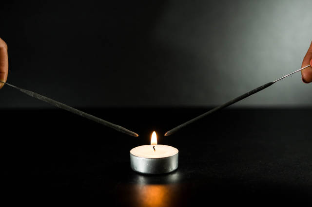 Two sparklers close to a candle flame