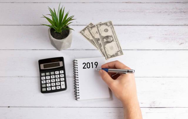 Konzeptbild zum Thema Budgetplanung im Jahr 2019, mit einem Stift in der Männerhand, Schreibblock, Taschenrechner und Dollarnoten