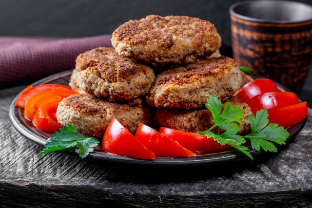 Fried cutlets with tomatoes and parsley on a wooden background