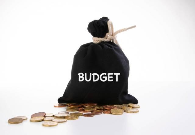 Schwarzer Geldsack mit Kleingeld und der Aufschrift Haushaltsbudget