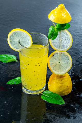 Cold yellow drink with fresh lemon and mint leaves on black background