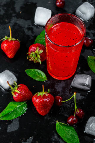 Red cocktail with ice cubes, strawberries and cherries on black background
