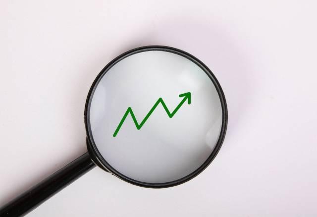 Grüne Pfeilgrafik zeigt aufwärts, vergrößert dargestellt unter einer Lupe
