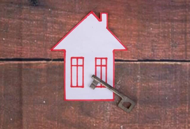 Vintage-Haustürschlüssel liegt auf einem selbstgemalten Haus