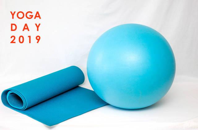 """Blaue Yogamatte und Gymnastikball vor weißem Hintergrund, mit dem Bildtitel """"Yoga Day 2019"""" - Tag des Yoga"""