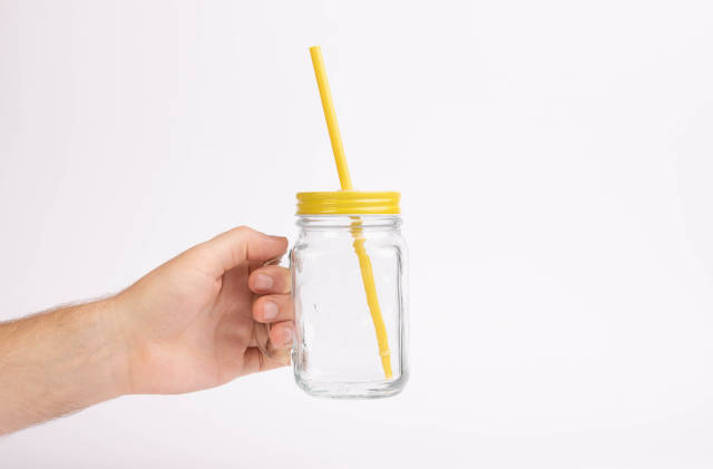 Hand holding glass with drinking straw