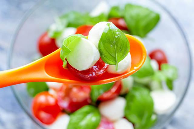 Close-up of Caprese salad in orange spoon