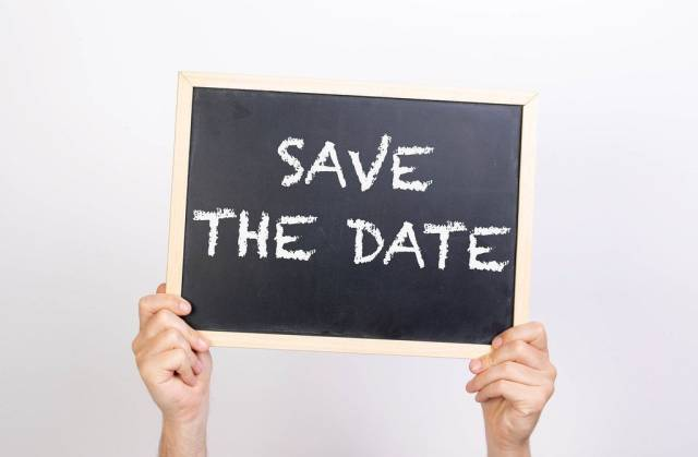 Hands holding blackboard with text Save the date