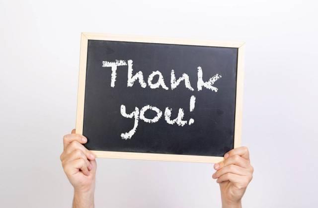 """Hände halten eine Kreidetafel hoch, mit dem Text """"Thank you"""" - Dankeschön"""