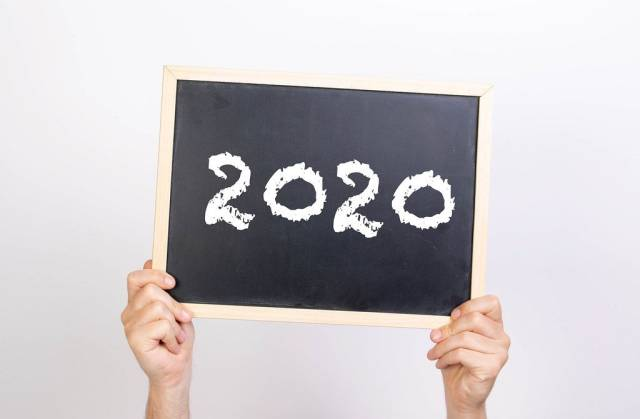 Hands holding blackboard with 2020 text