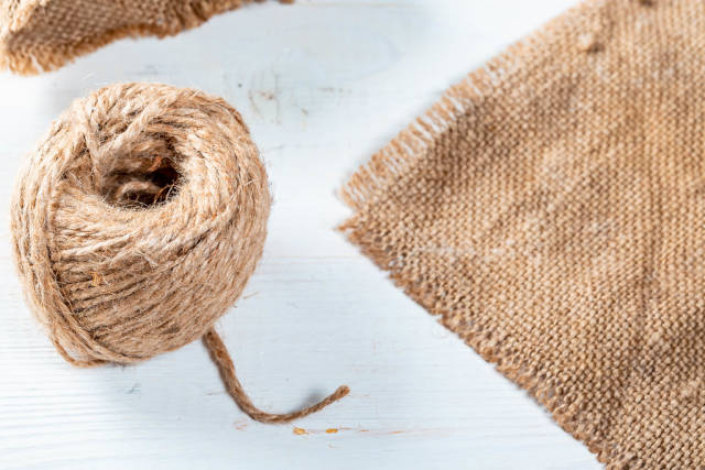 A piece of burlap fabric and a ball of thread