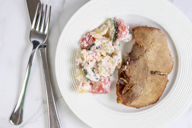 Flat lay above Baked Pork Chop with Serbian Sopska Salad