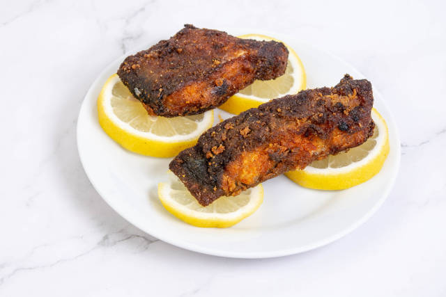 Pieces of fried Carp fish with Lemons on the plate
