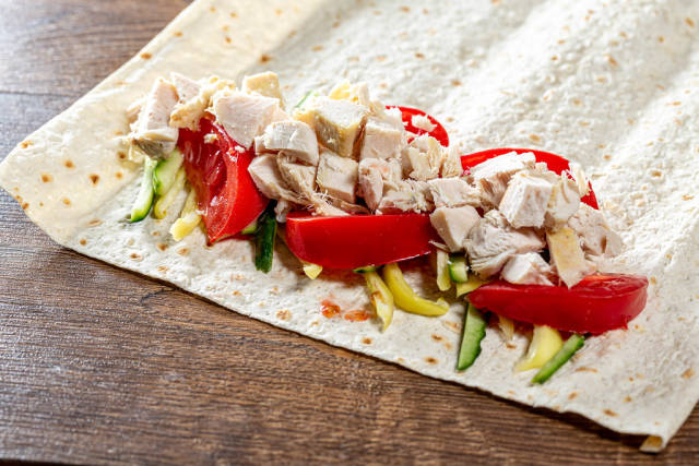 Chopped vegetables and meat on pita bread