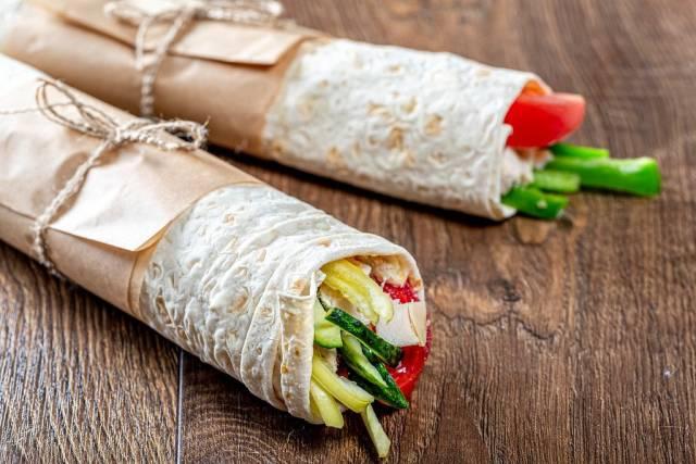 Zwei vorbereitete und gerollte Shawarma mit Gemüse und Hähnchen auf Holztisch