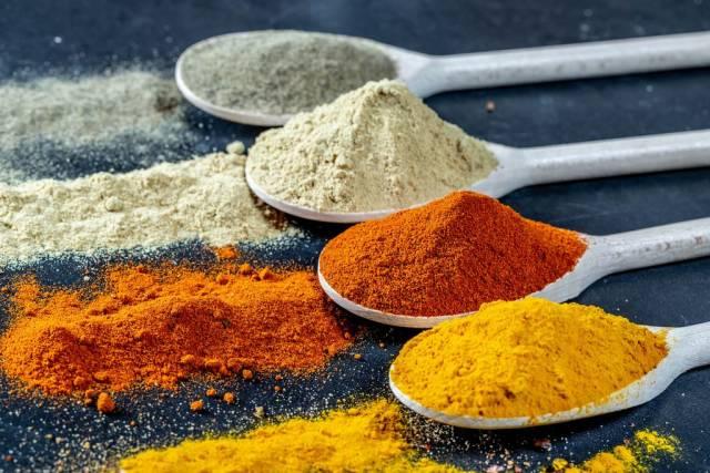 Hölzerne Löffel mit fein gemahlenen Gewürzen aus Indien wie Chili, Koriander, Kurkuma und Ingwer