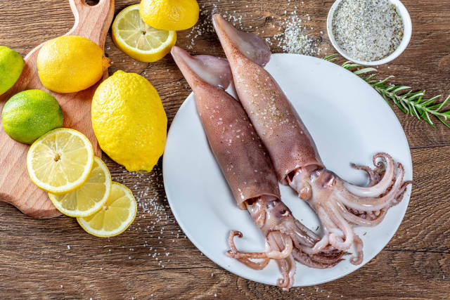 Two fresh squid on a plate with lemon, lime and rosemary