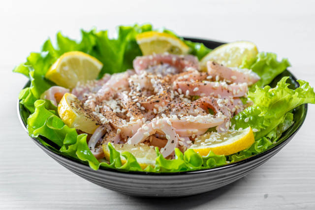 Salad with seafood and lettuce in a black bowl on a white table