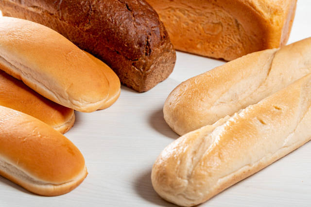Wheat bread, rye bread, baguettes and buns for hot dogs on white wooden background