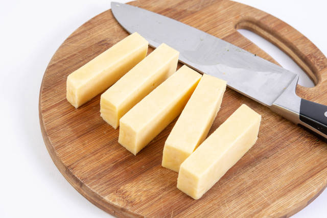 Sliced Cheddar Cheese on the kitchen wooden board