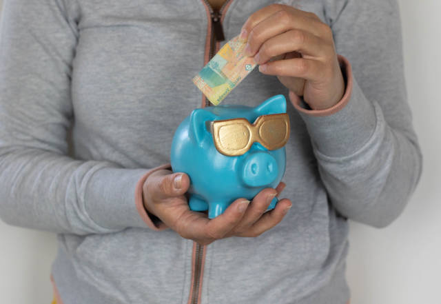 Frau legt Geld in die Urlaubskasse