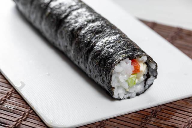 Rolling sushi maki. Preparation of Maki rolls with salmon