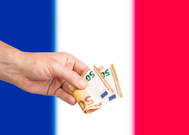 Hand with Euro banknotes over flag of France