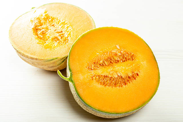Two halves of ripe orange melon with seeds inside