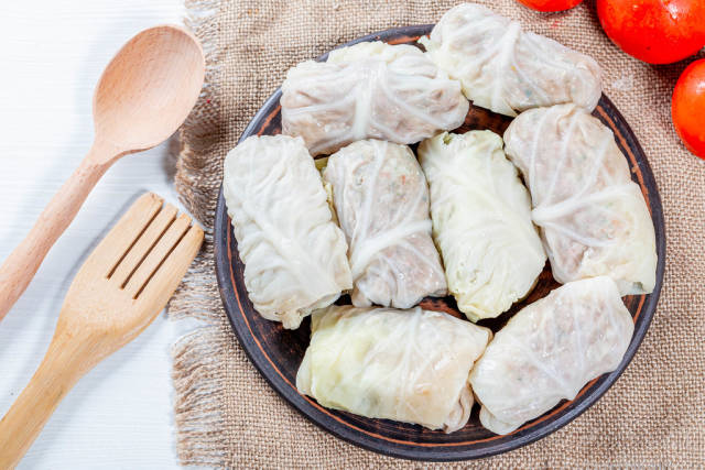 Cabbage rolls with meat and rice on burlap with wooden spoon and fork