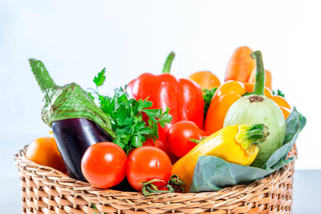 Carrots, bell peppers,balajan, tomatoes, zucchini and parsley in a wicker basket close-up